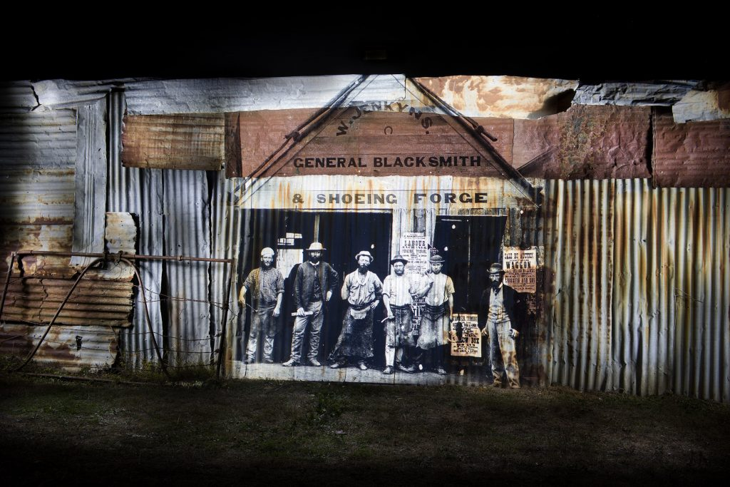 . La Paloma Pottery shed on Thomas Street. This tin wall was the perfect material to project the W. Jenkyns General Blacksmith shop image. I love the way the rust gave some of the fellas in this projection a lovely brown sepia tone.